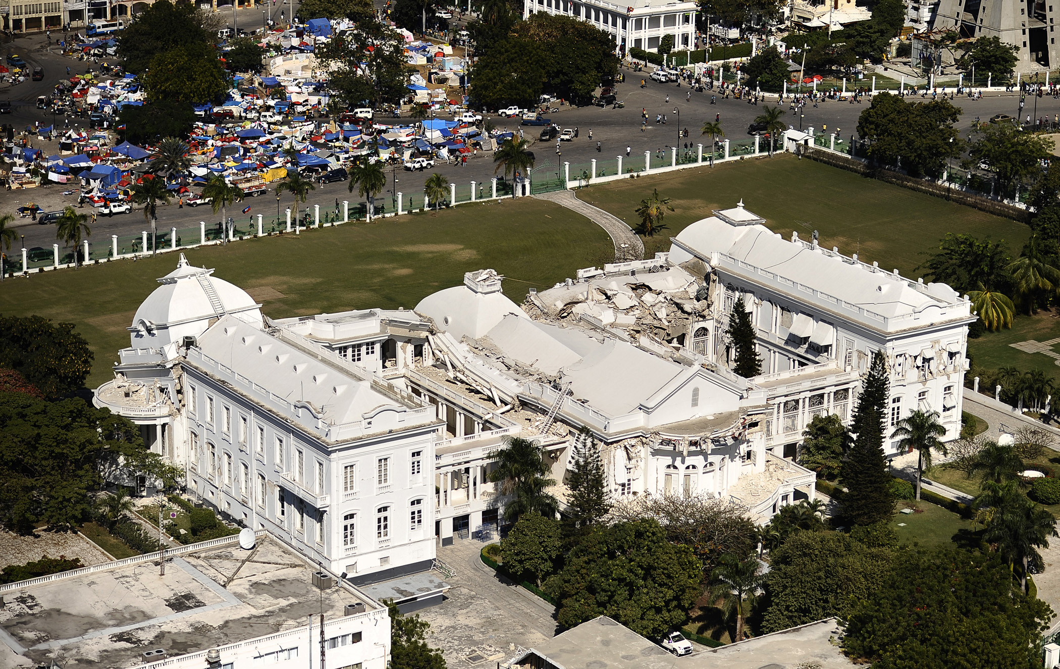 US_Navy_100128-N-5345W-277_The_Presidential_Palace_sits_in_ruins_while_hundreds_of_displaced_Haitians_take_shelter_in_one_of_the_many_tent_cities_just_outside_the_palaces_main_gate